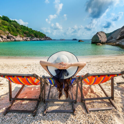 Woman with hat sitting on chairs beach in beautiful tropical bea