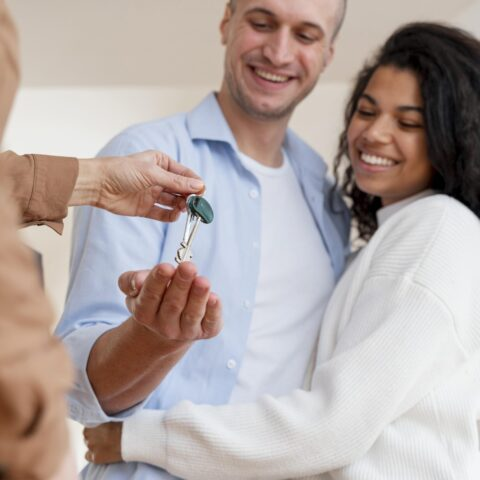 happy-couple-receiving-keys-their-new-home-from-realtor